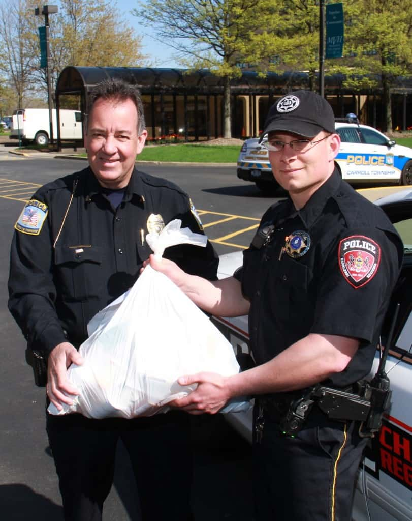 Carroll Twp. Police Chief Paul Brand and Officer Ryan Brand of Charleroi display one of the bags of drugs donated to the 6th National Drug Take Back Day in April.