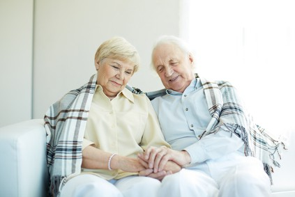 Portrait of cheerful senior couple sitting at home